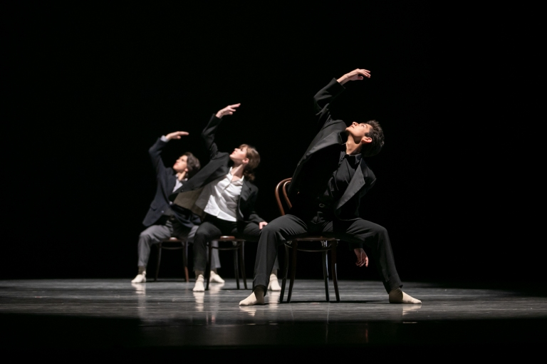 Three PNB School students dancing in Amanda Morgan's Pages. They are wearing untucked shirts, open suit jackets, and pants, and sit on wooden chairs facing out. Their right arms are outstretched overhead and the dancers are looking at their right hands. They are spotlighted from overhead against a dark stage. Photo © Lindsay Thomas