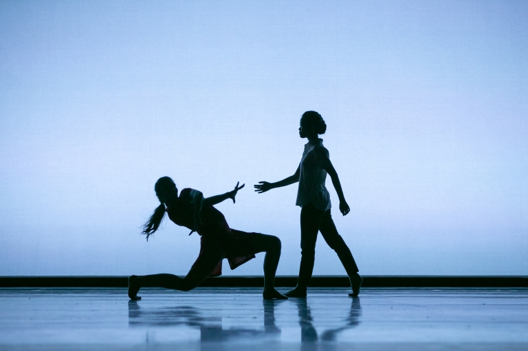 Two PNB School students dance in silhouette against a blue-grey backdrop in Amanda Morgan's Pages. Photo © Lindsay Thomas